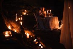 Jong paar die van een romantisch diner genieten door kaarslicht, in openlucht stock afbeeldingen