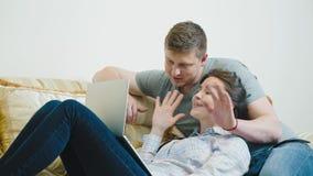 Jong paar die videopraatje met familie over laptop hebben stock videobeelden