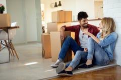 Jong paar die zich in nieuw huis en uitpakkende carboard dozen bewegen royalty-vrije stock afbeeldingen