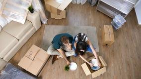 Jong paar die zich in nieuw huis en uitpakkende carboard dozen bewegen stock foto