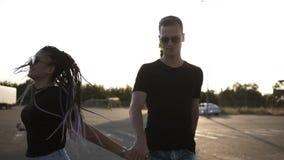Jong paar - donkerbruin dreadlocksmeisje in zonnebril en haar vriend lopen, die handen houden De zon glanst op stock video
