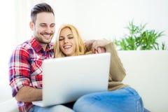 Jong paar doorbladerend Internet thuis, het gebruiken van laptop en het glimlachen Royalty-vrije Stock Afbeelding
