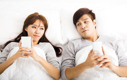 Jong paar in een bed met slimme telefoons stock afbeelding