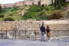 Jong paar: een kerel en een meisje met een rugzak die het Roman theater van Malaga bezoeken ruïne stock afbeeldingen