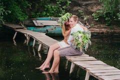 Jong paar in een kroon met een boeket op het houten brug lachen Royalty-vrije Stock Foto