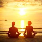 Jong paar in een lotusbloempositie die op het strand mediteert Stock Afbeelding