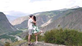 Jong paar een man en een vrouw die tegen de achtergrond van de bergen koesteren Romantische reis stock footage
