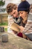 Jong paar in het kader van algemeen lezingsboek in openlucht Stock Afbeelding