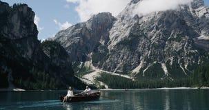 Jong paar in het midden van meer in het houten boot ontspannen op zonnige dag, die samen reizen Langzame Motie stock footage