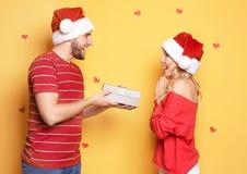 Jong paar in Kerstmanhoeden met Kerstmisgift Royalty-vrije Stock Afbeelding
