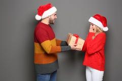 Jong paar in Kerstmanhoeden met Kerstmisgift Stock Fotografie