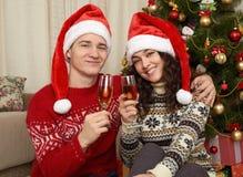 Jong paar in Kerstmisdecoratie Huisbinnenland met giften en spar Het nieuwe concept van de jaarvakantie Liefde en tederheid Royalty-vrije Stock Foto