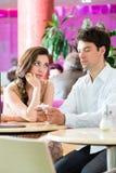 Jong paar in koffie die maar op telefoon op elkaar inwerken niet Stock Afbeeldingen