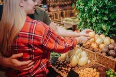 Jong paar in kruidenierswinkelopslag Hij omhelst haar Zij richt op exotisch fruit in mand Besnoeiingsmening stock afbeelding