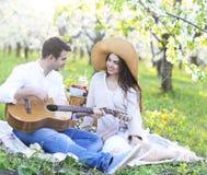 Jong paar in liefde bij picknick in de tuin van de de lentebloesem Stock Fotografie
