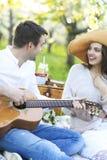 Jong paar in liefde bij picknick in de tuin van de de lentebloesem Stock Foto