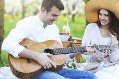 Jong paar in liefde bij picknick in de tuin van de de lentebloesem Stock Foto's