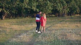 Jong paar in liefde buiten de stad in aard bij zonsondergang stock video