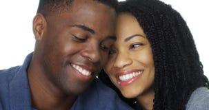 Jong paar in liefde die en camera glimlacht bekijkt Stock Afbeelding