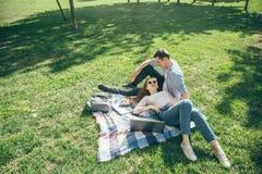Jong paar in liefde die op het gazon na school op een Zonnige dag rusten stock afbeeldingen