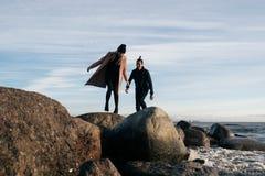Jong paar in liefde die over stenen in water springen De gelukkige minnaars hebben pret op het strand stock fotografie