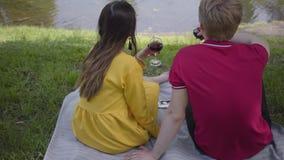 Jong paar in liefde die picknick met wijn in mooie bloeiende tuin of en park maken die cheerfully babbelen glimlachen datum stock video