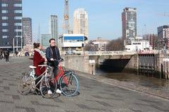 Jong paar in liefde met toeristen die in Rotterdam met hun fietsen op een de herfstdag reizen binnen bezoekend de haven en de riv royalty-vrije stock afbeeldingen