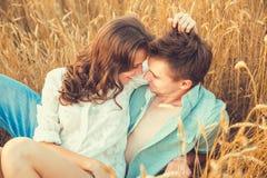 Jong paar in liefde openlucht D Het Koesteren van het paar Jong mooi paar in liefde die en op het gebied op zonsondergang blijven royalty-vrije stock foto's