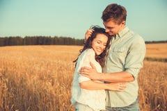 Jong paar in liefde openlucht Het Koesteren van het paar Jong mooi paar in liefde die en op het gebied op zonsondergang blijven k Royalty-vrije Stock Fotografie