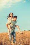 Jong paar in liefde openlucht Het Koesteren van het paar Jong mooi paar in liefde die en op het gebied op zonsondergang blijven k Royalty-vrije Stock Afbeeldingen