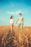 Jong paar in liefde openlucht Het Koesteren van het paar Jong mooi paar in liefde die en op het gebied op zonsondergang blijven k Stock Fotografie