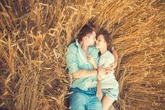 Jong paar in liefde openlucht Het Koesteren van het paar Jong mooi paar in liefde die en op het gebied op zonsondergang blijven k Royalty-vrije Stock Afbeelding