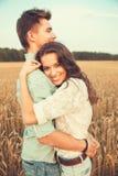 Jong paar in liefde openlucht Het Koesteren van het paar Jong mooi paar in liefde die en op het gebied op zonsondergang blijven k Stock Afbeeldingen