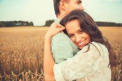 Jong paar in liefde openlucht Het Koesteren van het paar Jong mooi paar in liefde die en op het gebied op zonsondergang blijven k Stock Afbeelding