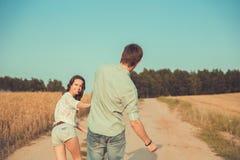 Jong paar in liefde openlucht Paarlooppas over het gebied Royalty-vrije Stock Afbeelding