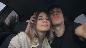 Jong paar in liefdekerel en girl do selfie in de auto De man koestert het meisje stock videobeelden