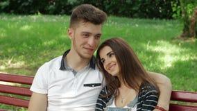 Jong paar in liefdeomhelzingen en het spreken op een bank stock video