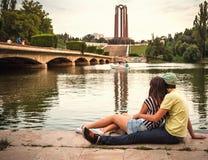 Jong paar in liefdezitting dichtbij meer in parklandschap stock foto's