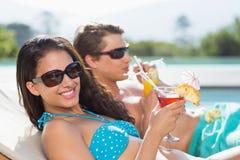 Jong paar met dranken door zwembad Stock Foto's