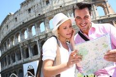 Jong paar met een kaart die zich dichtbij Coliseum van Rome bevinden royalty-vrije stock afbeelding