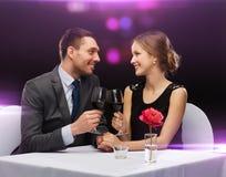 Jong paar met glazen wijn bij restaurant stock afbeelding
