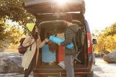 Jong paar met het kamperen materiaal dichtbij autoboomstam royalty-vrije stock afbeelding