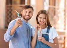 Jong paar met koppen van heerlijke milkshake Royalty-vrije Stock Afbeelding