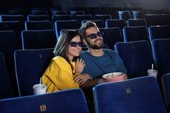 jong paar met popcorn het letten op film stock afbeelding