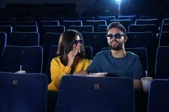 jong paar met popcorn het letten op film in bioskoop stock afbeelding