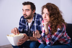 Jong paar met popcorn het letten op film op TV Stock Foto