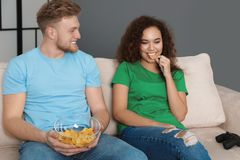 Jong paar met snack en videospelletjecontrolemechanisme royalty-vrije stock afbeelding