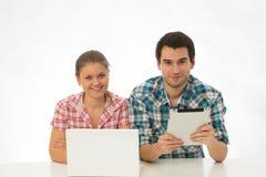 Jong paar met tablet en PC stock fotografie