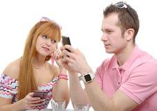Jong paar met telefoons op wit Stock Fotografie