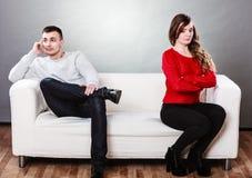 Jong paar na ruziezitting op bank Stock Fotografie